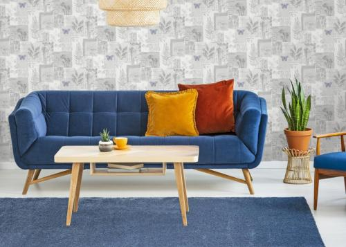 Armchair next to blue sofa with cushions and wooden table in fla